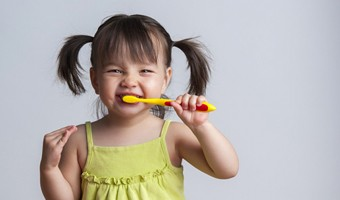 Little girl brushes her teeth after visiting Annapolis family dentist near me