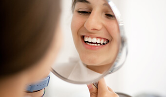 reflection of woman smiling in mirror