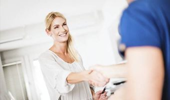 A woman shaking hands with a dental employee