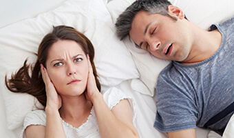 woman covering ears to block snoring from husband