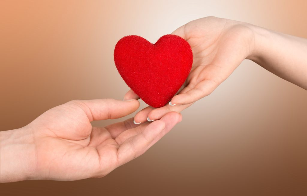 One person giving a small heart to another person