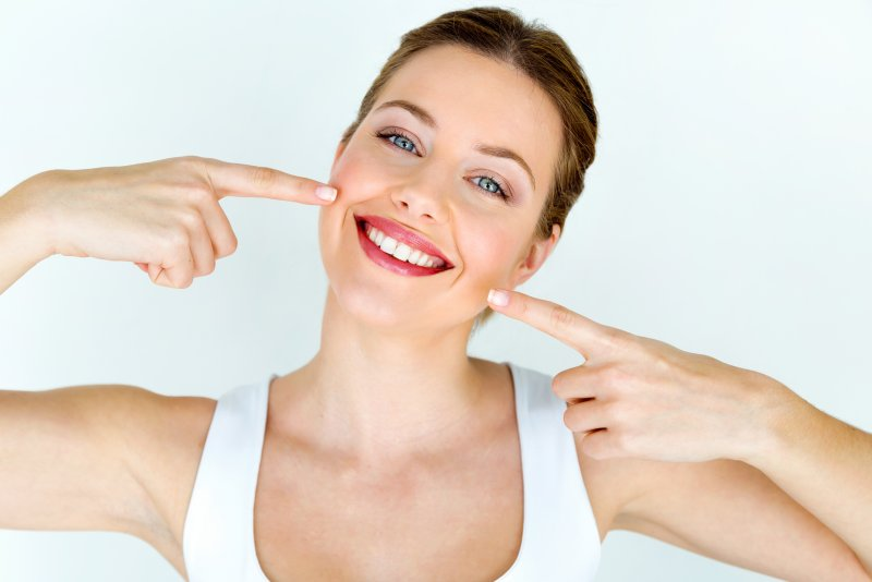 woman smiling pointing at teeth